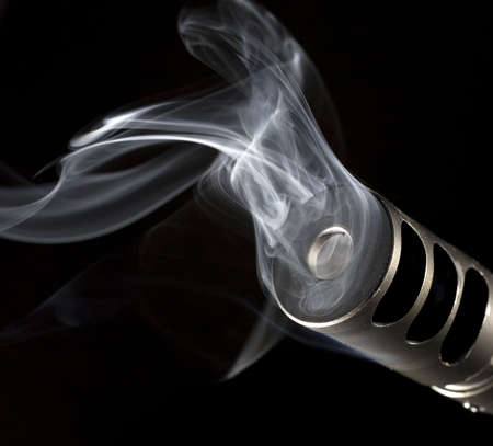 muzzle on a rifle that has smoke pouring out from it Stock Photo