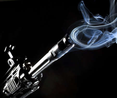 assault rifle that has smoke rings coming out of its barrel Stock Photo