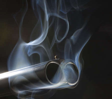 연기를 뿜어내는 엽총의 두 배럴