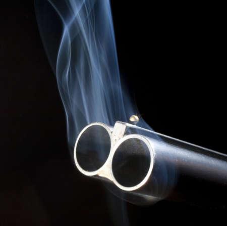 Both barrels of a double barreled shotgun belching smoke after shooting photo
