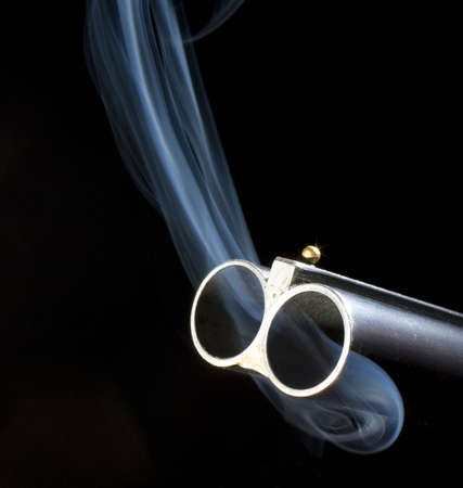 Both barrels of a double barrel shotgun billowing smoke