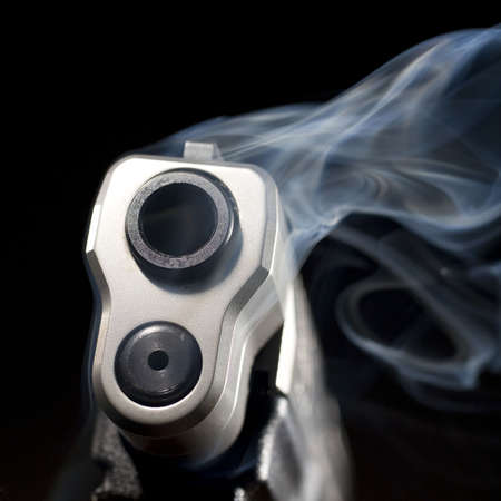 muzzle: Blue smoke that is rising from the muzzle of a handgun