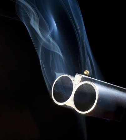 double barreled shotgun with smoke coming out of both barrels Archivio Fotografico