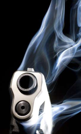 gun barrel: Pistol in the dark with lots of blue smoke rising Stock Photo