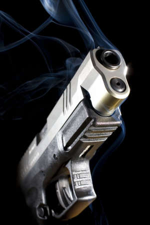 Handgun that has been shot so much smoke is pouring out