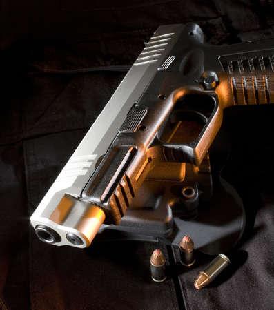Handgun on a vest with orange side light and cartridges around
