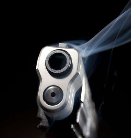 Smoking gun that is still releasing blue smoke on black 版權商用圖片 - 7493259