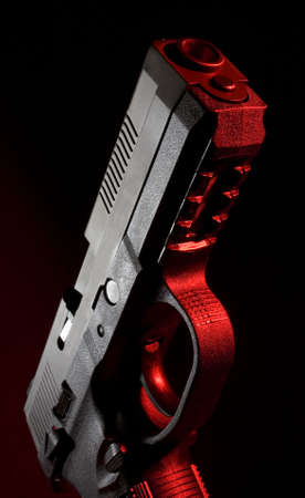 Polymer pistol on black with a red gel applied to the gun