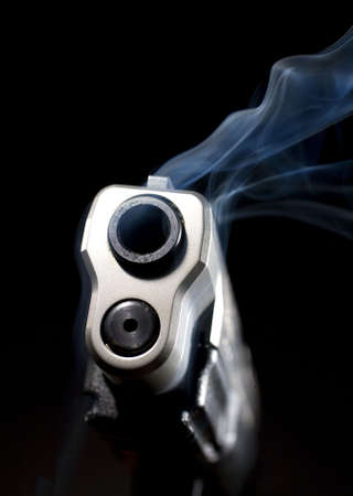 Barrel of a steel handgun that is so hot it is smoking