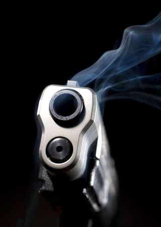 Barrel of a steel handgun that is so hot it is smoking