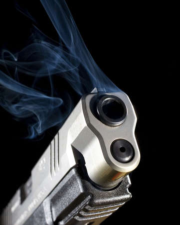 Semi-automatic pistol releasing smoke after a shot has been taken