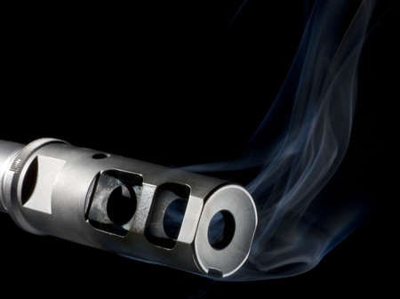 flash hider: Flash hider on an assault weapon that is pouring out smoke