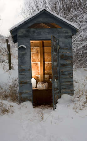 outhouse: Out house in the backcountry that is covered in snow and ice Stock Photo