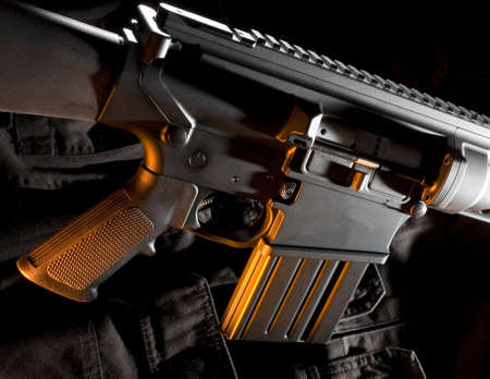 assault rifle that is black with an orange color from the side