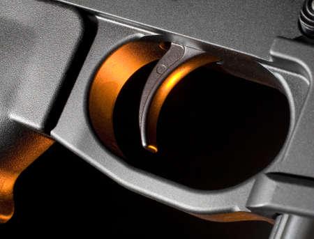 gatillo: gel naranja aplicado desde detr�s de un desencadenador de fusiles de asalto Foto de archivo