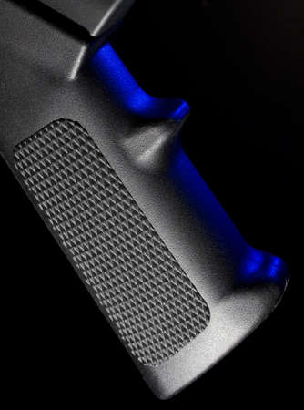 grip: Pistol grip on an assault rifle with a blue gel at the side Stock Photo