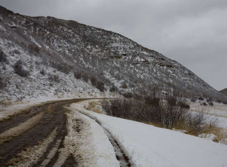 mud and snow: Remote mountain road that is covered in a fresh snow
