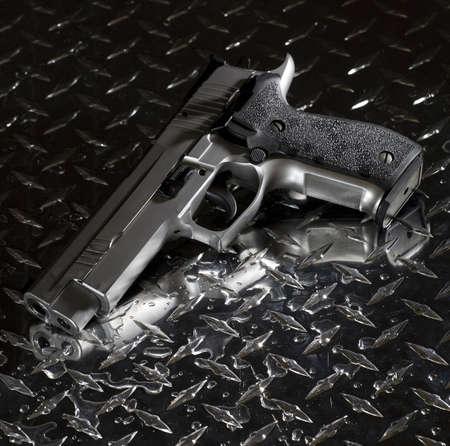 Semi automatic handgun that is on a wet piece of steel Stok Fotoğraf