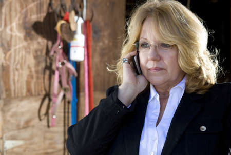 important phone call: Woman that is taking an important cell phone call in the barn