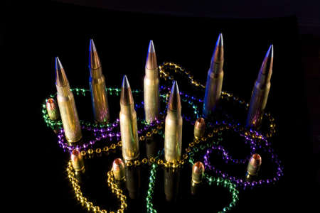 fat tuesday: Big and fat ammunition surrounded by Mardi Gras beads for Fat Tuesday