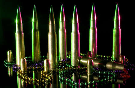 Fifty caliber ammunition with Mardi Gras beads and one cartridge is sick 版權商用圖片