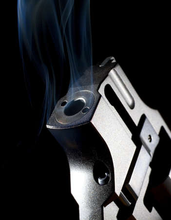 Revolver pointed up that has smoke coming from its barrel Banco de Imagens