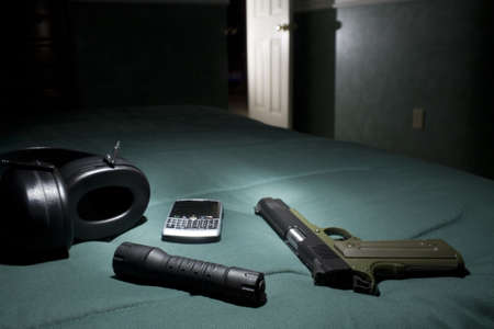 bedspread: Handgun, flashlight, cell phone and hearing protection on a bed