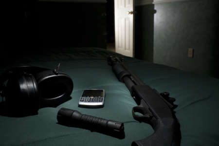 bedspread: Shotgun, cell phone, flashlight and hearing protection waiting in the bedroom Stock Photo