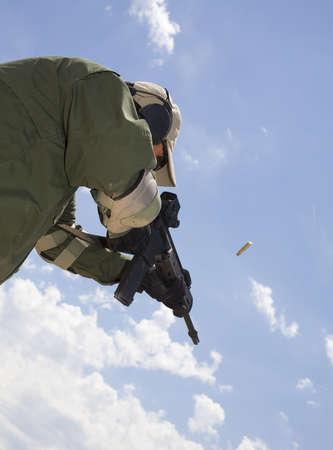 flash hider: Hombre visto desde abajo disparando un rifle de asalto de bronce en el aire Foto de archivo