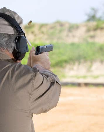 촬영 범위에서 반 자동 권총을 사용하는 사람 (남자)