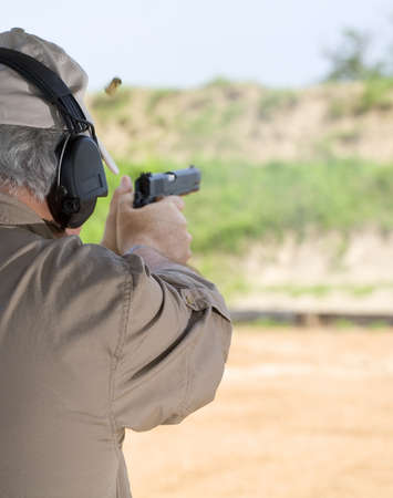Man using a semi automatic pistol at the shooting range