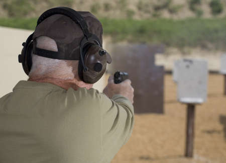 Handgun shooter readying to shoot at steel targets Stock Photo