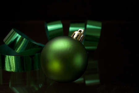 Green Christmas bulb and green ribbon on a black background Stock Photo