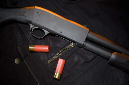 Orange gel from above on a pump action shotgun and ammunition Stock Photo