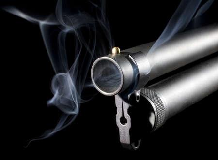 Shotgun that has blue smoke coming from its 12 gauge barrel