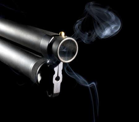 Barrel of a shotgun that is still smoking after a shot photo