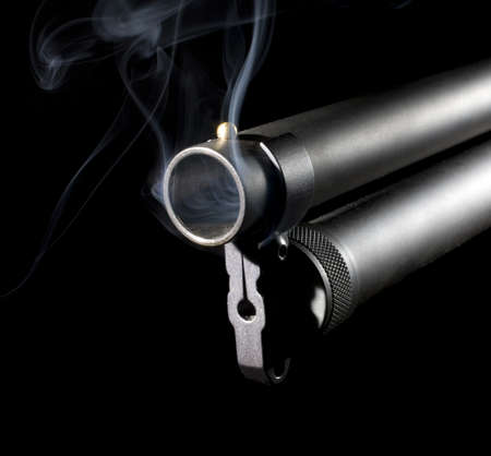 Shotgun with an extended magazine with smoke coming from the muzzle photo