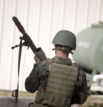 Military man with a suppressor on his rifles muzzle