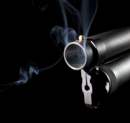 Twelve gauge shotgun that has smoke coming from its barrel