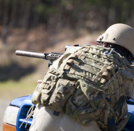 suppressed: Shooter taking shots with a suppressed modern sporting rifle Stock Photo