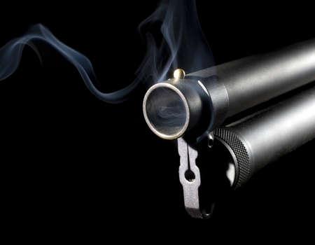 Big shotgun that has blue smoke coming from its barrel photo