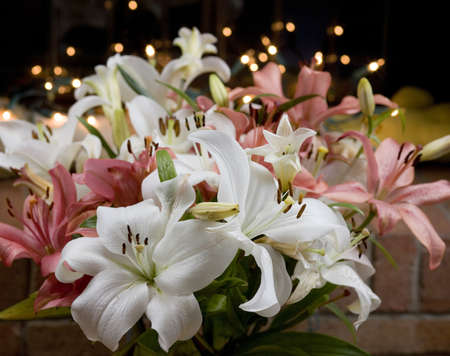 Arrangement of white and purple lillies with lights glowing behind photo