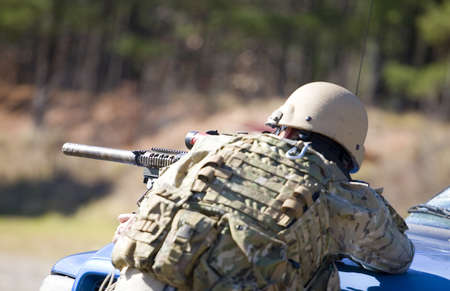 Rifle that has a silencer on its muzzle being used for a shot