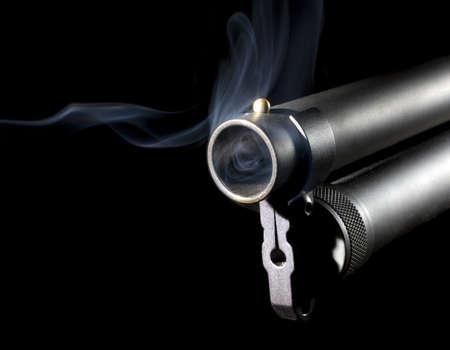 Twelve gauge shotgun that has blue smoke around its barrel photo