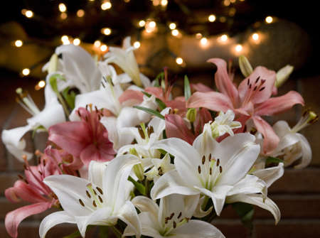 lillies: Arrangement of flowers with lights behind for a party Stock Photo