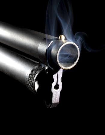 Shotgun that is hot enough to have smoke coming from the muzzle photo