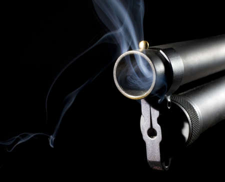 Shotgun that is blowing smoke after is has been used to shoot photo