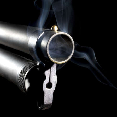 Shotgun that has smoke near and inside of its barrel on black photo