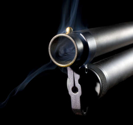 Muzzle of a twelve gauge shotgun that has smoking coming out Stock Photo