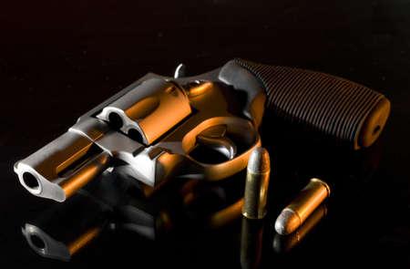 오른쪽 측면에서 오렌지 빛 유리 서랍장에 권총